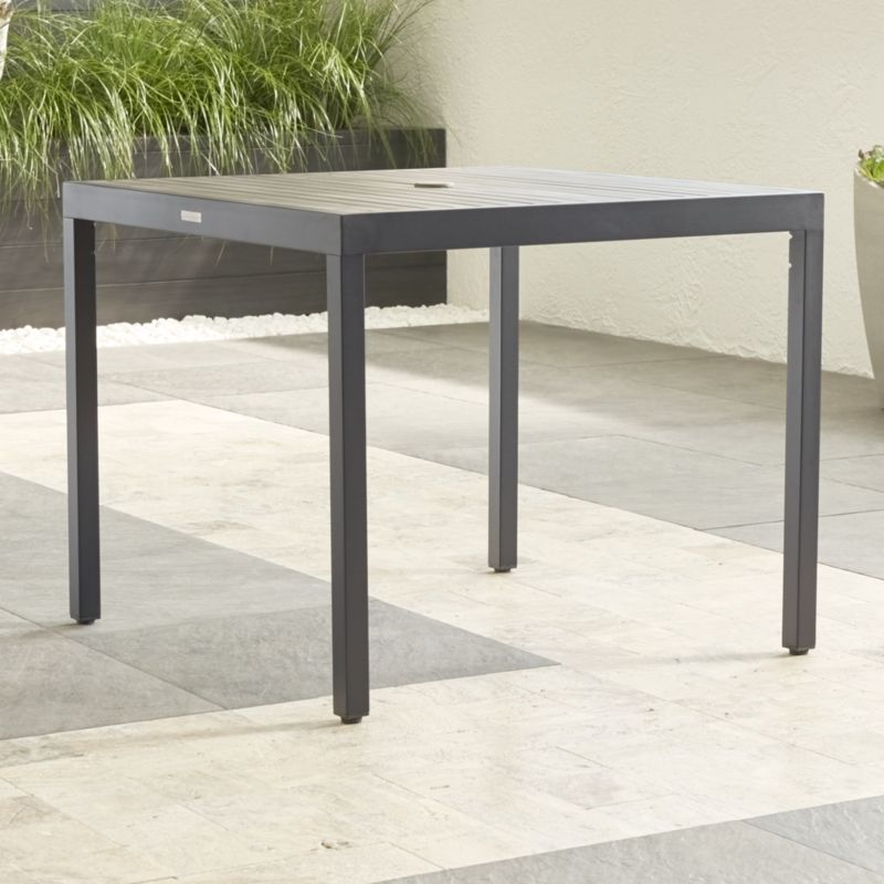 Casual and stylish outdoor café table fools the eye with the look of real wood and fools the elements with UV- and fade-resistant qualities. Slats of innovative warm grey polystyrene faux wood are treated with UV and anti-oxidant protection. <NEWTAG/><ul><li>Extruded polystyrene with UV and anti-oxidant protection</li><li>Aluminum frame with powdercoat finish</li><li>Levelers</li><li>Seats 4</li><li>Umbrella opening with self-storing plug</li><li>Made in China</li></ul><br />
