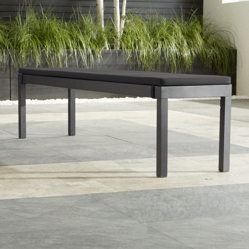 This casual and stylish outdoor dining collection fools the eye with the look of real wood and fools the elements with UV- and fade-resistant qualities. The dining bench is crafted in slats of innovative warm grey polystyrene faux wood and features a durable black powdercoated aluminum frame.<NEWTAG/><ul><li>Extruded polystyrene with UV and anti-oxidant protection</li><li>Aluminum frame with powdercoat finish</li><li>Fade- and mildew-resistant Sunbrella acrylic</li><li>Foam cushion fill</li><li>Fabric tab fasteners</li><li>Seats 4</li><li>Made in China and USA</li></ul><br />
