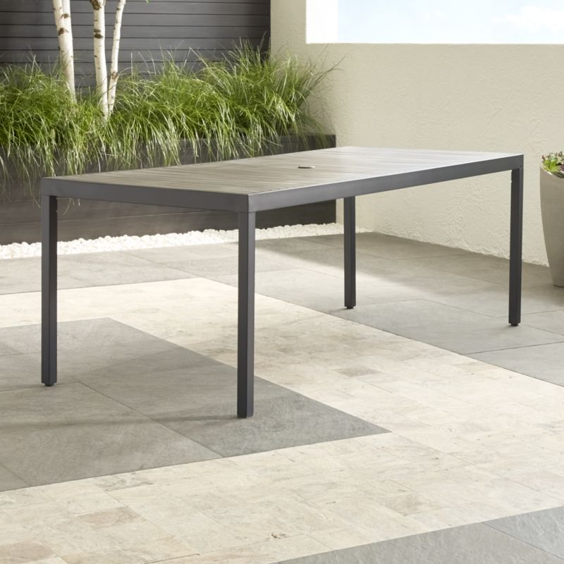 Our casual, stylish Alfresco rectangular dining table fools the eye with the look of real wood just as it fools the elements with UV- and fade-resistant qualities. Innovative warm grey faux wood slats are treated with UV and anti-oxidant protection. <NEWTAG/><ul><li>Extruded polystyrene with UV and anti-oxidant protection</li><li>Aluminum frame with powdercoat finish</li><li>Levelers</li><li>Seats 8</li><li>Umbrella opening with cover</li><li>Made in China</li></ul><br />