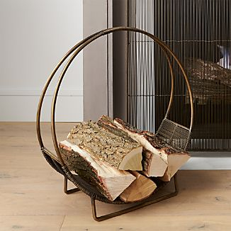 Hoop-shaped holder stacks a clean round of logs, with a basket-like bottom to hold in stray twigs and bark. Handcrafted of iron with antiqued brass and clear powdercoat finishes.