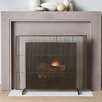 Mid-century modern styling screens the hearth in handcrafted iron with a warm, antiqued brass finish. Freestanding, footed screen is rich with texture in both the wire construction and the patina.