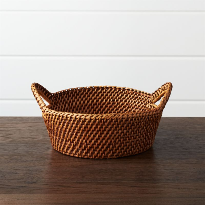Handcrafted of 100% rattan, the Artesia serving collection is woven in a pattern known as hapao. Originating in a remote village in northern Luzon, the largest island in the Philippines,  hapao is a traditional pattern used for bags and baskets. Over time, the colors used and shapes formed changed, though always emphasizing the durability and natural beauty of this amazing fiber. Each piece in the Artesia collection is finished in beautiful honey brown, calling out the texture and intricacy of the weave and bringing warm color to the table. Ear handles with braid detailing on the rim accent this small-sized basket, perfect for serving crackers and rolls.<br /><br /><NEWTAG/><ul><li>Handcrafted</li><li>100% rattan</li><li>Non-toxic, food-safe coating</li><li>Clean with dry or damp cloth</li><li>Made in The Philippines</li></ul>