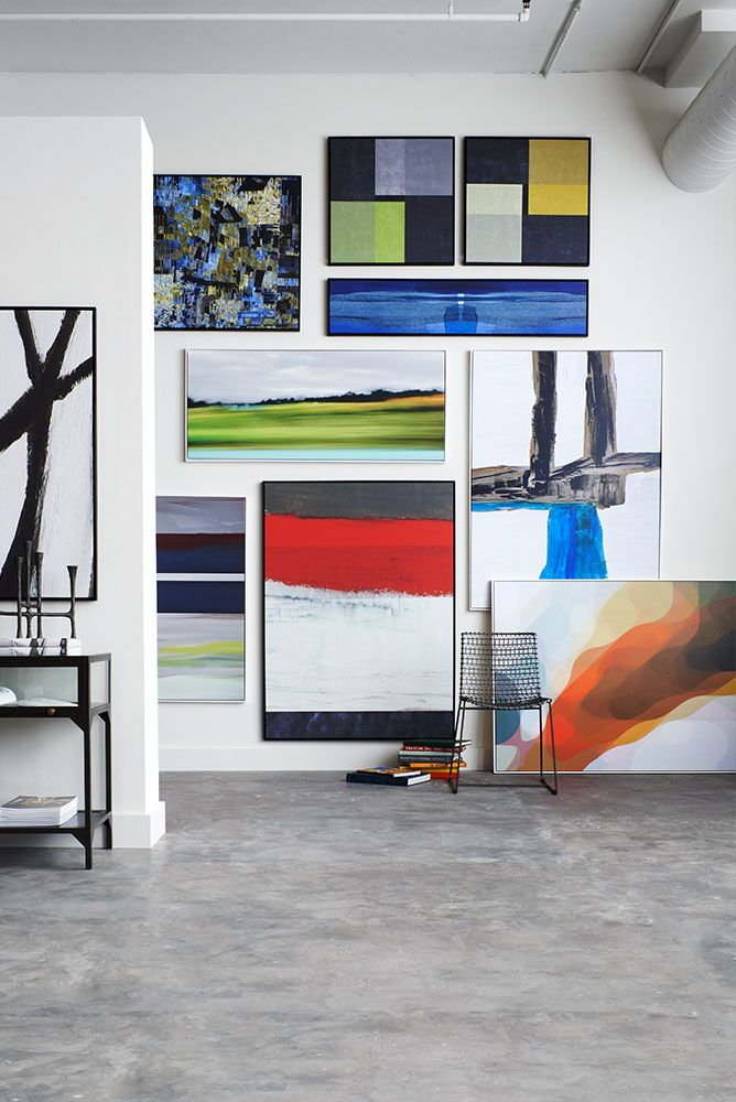 Artworks framed prints hanging on a white wall in a loft with a concrete floor.