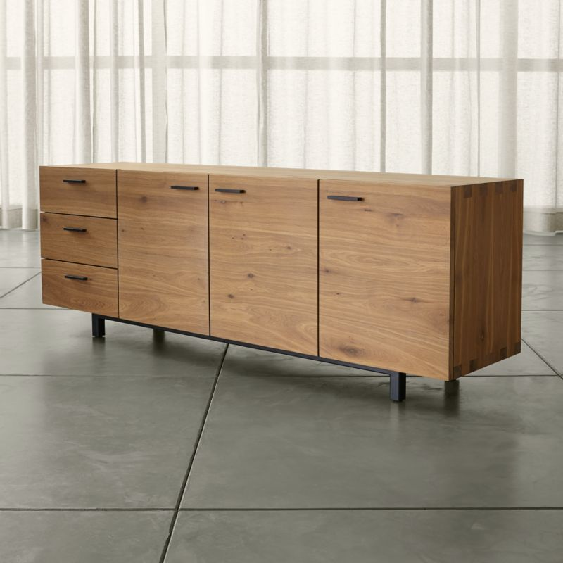 This expertly crafted sideboard reaches new heights in a clean-lined, low-profile design that emphasizes the wood's rich grain and warm color. Aspen's slim, horizontal pulls of blackened steel accent three doors and three drawers, which provide abundant storage. <NEWTAG/><ul><li>Solid white European oak with smoke finish</li><li>Solid finger joinery</li><li>One large and one small adjustable shelf</li><li>Blackened steel pulls</li><li>Soft closing glides</li><li>Cold-pressed steel legs with levelers</li><li>Made in Poland</li></ul><br />