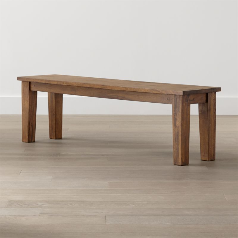 Displaying the heft and character of a European farmhouse antique, this mid-sized bench echoes the simple and rustic character of our Basque dining collection. Hand-planed planks of sustainable solid mango wood are enhanced with peg detailing lend unmistakable authenticity to the expert craftsmanship. <NEWTAG/><ul><li>Sustainable solid mango wood</li><li>Rich honey stain with lacquer and wax finish</li><li>Hand-planed wooden planks</li><li>Peg detailing</li><li>Naturally occurring grain and knots</li><li>Seats 3</li><li>Made in India</li></ul><br /><br />