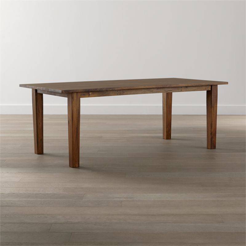 "Handcrafted of sustainable solid mango wood, the Basque 82"" dining table recalls the heft and character of a European farmhouse antique. Simple and rustic, this dining table's bold proportions are enhanced with a rich waxed honey finish. <NEWTAG/><ul><li>Sustainable solid mango wood</li><li>Rich honey stain with lacquer and wax finish</li><li>Hand-planed wooden planks</li><li>Peg detailing</li><li>Naturally occurring grain and knots</li><li>Seats 8</li><li>Made in India</li></ul>"