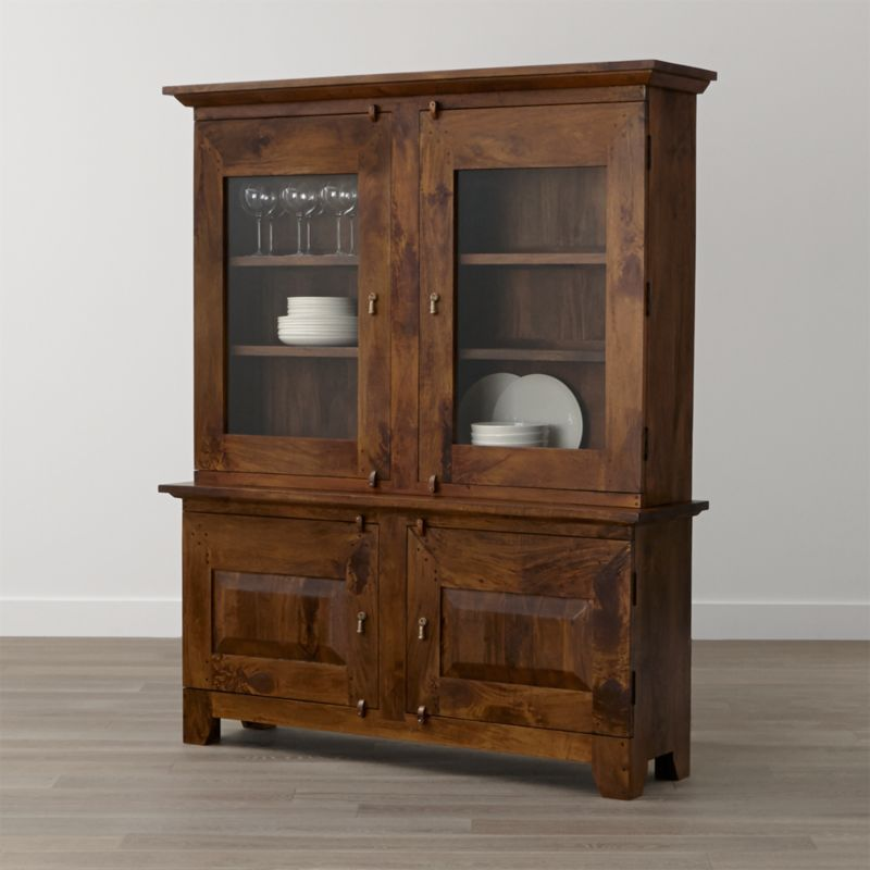 Simple and rustic, our Basque dining room storage duo recalls the heft and character of European farmhouse antiques. This boldly proportioned buffet and hutch are handcrafted entirely of sustainable solid mango wood with a combination of glass panel and wood doors, cast brass pulls and rustic hasp closures. Authentic peg detailing and a rich waxed honey finish highlight the wood's natural open grain and the beautifully unique knots of each hand-planed plank. <NEWTAG/><ul><li>Sustainable solid mango wood</li><li>Rich honey stain with lacquer and wax finish</li><li>Hand-planed wooden planks</li><li>Naturally occurring grain and knots</li><li>6 fixed shelves: 2 in buffet, 2 per side in hutch</li><li>Cast brass pulls and hasp closures</li><li>Made in India</li></ul>