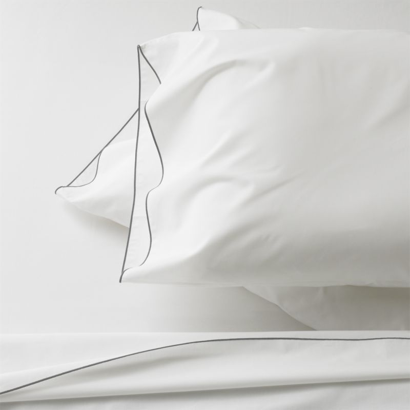 Clean, basic white bedding upgrades in soft, smooth cotton percale, beautifully contrasted with a graceful grey overlocking stitch on the flat sheet and pillow case. Generous fitted sheet pockets accommodate thicker mattresses. Sheet set includes one flat sheet, one fitted sheet and two king pillow cases. Bed pillows also available.<br /><br /><NEWTAG/><ul><li>100% cotton percale</li><li>200-thread-count</li><li>Machine wash; tumble dry low</li><li>Made in Portugal</li></ul>