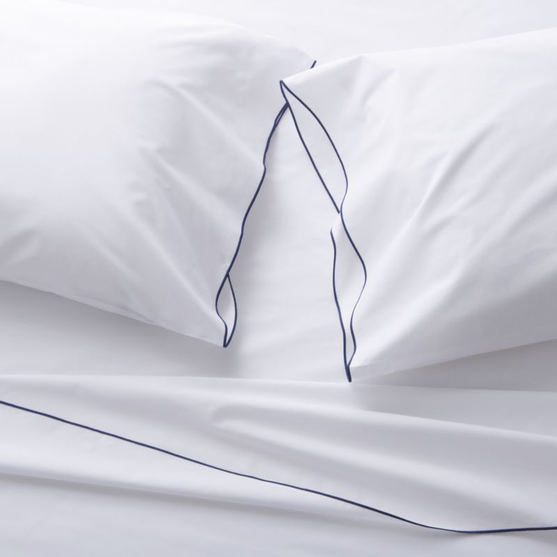 Clean, basic white bedding upgrades in soft, smooth cotton percale, beautifully contrasted with a graceful blue overlocking stitch on the flat sheet and pillow case. Generous fitted sheet pockets accommodate thicker mattresses. Sheet set includes one flat sheet, one fitted sheet and one standard pillow case. Bed pillows also available.<br /><br />This product is certified by Oeko-Tex®, an international association focused on textile safety and sustainable production. Oeko-Tex® tests for known harmful substances and chemicals as well as for acidity and color fastness. All components of the product must comply with stringent Oeko-Tex® standards to achieve certification.<br /><br /><NEWTAG/><ul><li>Certified by Oeko-Tek</li><li>100% cotton percale</li><li>200-thread-count</li><li>Machine wash; tumble dry low</li><li>Made in Portugal</li></ul>