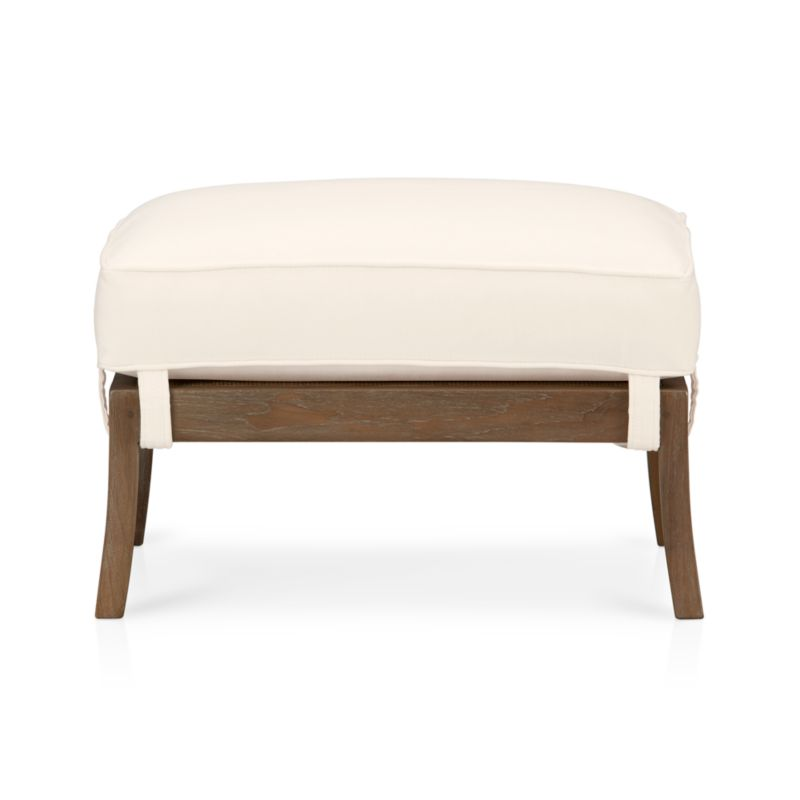 """We've freshened up our popular solid teak and handwoven rattan lounge seating with a soft grey wash and white cotton-poly cushions. And, more importantly, we've given it an eco-friendly upgrade: The frame is crafted of plantation-grown teak supported by TFT, a nonprofit organization that promotes responsible forest management, and the 4½""""-thick cushioning is multilayer soy- or plant-based polyfoam. Ottoman shows off the same great flared leg as the chair, cushion straps at the corners and underlying rattan mesh.<br /><br /><NEWTAG/><ul><li>Solid teak harvested from plantations working with TFT and woven rattan mesh</li><li>Grey wash finish</li><li>Nylon webbing suspension</li><li>Cotton-polyester cushion with multilayer soy- or plant-based polyfoam</li><li>Professional cushion cleaning recommended</li><li>Made in Indonesia and USA</li></ul>"""