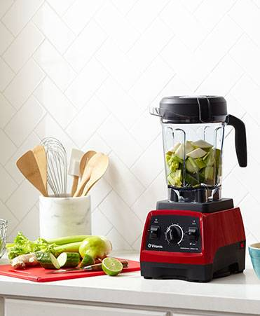 Red Vitamix next to a marble kitchen utensil holder and a red cutting board covered in a variety of green produce.