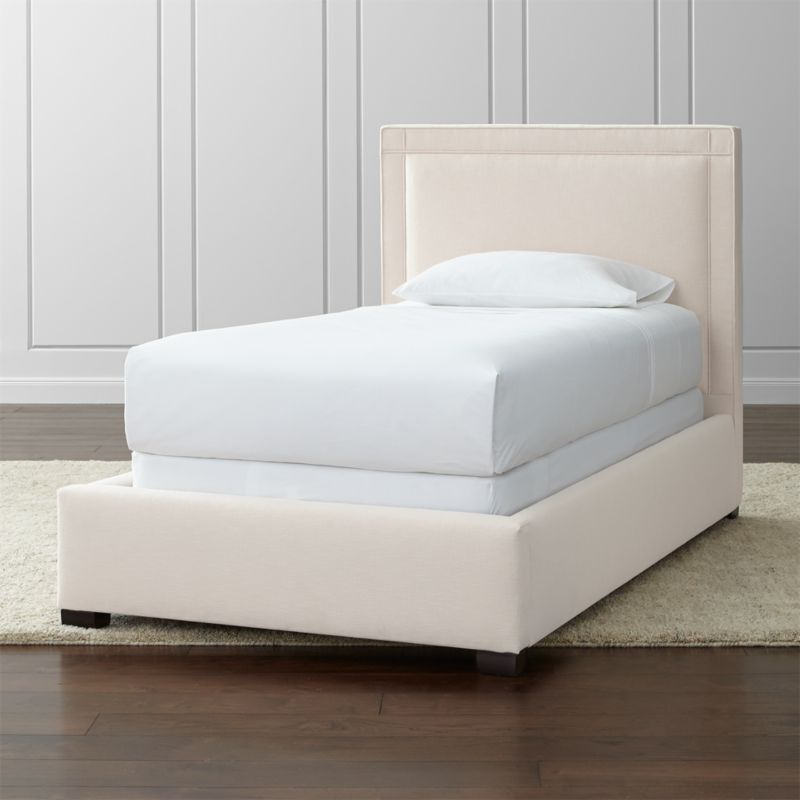 "The Border twin bed's square sensibility takes the edge off in a soft neutral cotton-poly blend over a linear frame. Self-welt detail adds architectural polish, outlining the perimeter of the twin bed with horizontal and vertical lines intersecting at each corner. <NEWTAG/><ul><li>Frame is benchmade with certified sustainable hardwood that's kiln-dried to prevent warping</li><li>Soy-based polyfoam cushioning</li><li>Solid maple legs with brown finish</li><li>3 metal slats with 3 center support legs</li><li>Accommodates <a href=""/furniture/mattresses-foundations/1"">mattress and box spring</a> (sold separately)</li><li>Maximum weight capacity: 500 lbs. (includes weight of mattress, box spring and occupants)</li><li>Made in North Carolina, USA</li></ul><br />"