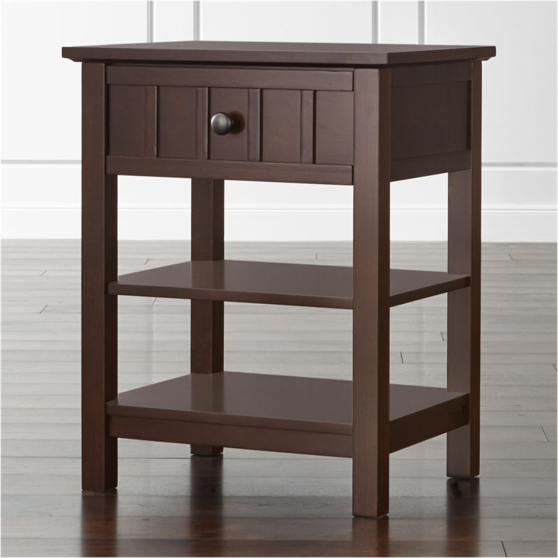 Designed by Blake Tovin of Tovin Design, our Brighton collection's casual nightstand modernizes classic cottage styling in a warm coffee hue with antique brass drawer pull. Stepped detail on the drawer front recalls the architectural board and batten detailing of the Brighton beds. <NEWTAG/><ul><li>Designed by Blake Tovin of Tovin Design</li><li>Solid poplar and engineered wood with coffee brown lacquer finish</li><li>Naturally expands and contracts with changes in humidity</li><li>1 drawer</li><li>2 open display shelves</li><li>Metal side-mounted glides</li><li>Antique bronze knob</li><li>Made in Vietnam</li></ul>