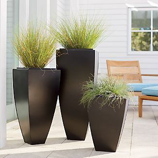 Tall, tapered planter is handcrafted in iron and finished in antiqued bronze with gold-highlighted edges. Double-walled planter has a removable planter insert with slightly higher profile. Base may be filled with sand or gravel for stability in outdoor settings. Rubber feet prevent slipping.100% ironAntiqued bronze finishDrainage holes with plugs providedNonslip feetFor indoor or outdoor use; bring indoors during freezing temperaturesMade in India