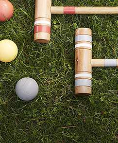 Croquet mallet and croquet balls laying down on grass