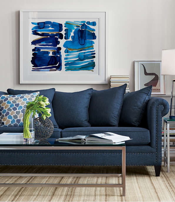 Living room featuring Durham Sofa in Sapphire, Era Rectangular Glass Coffee Table, Lynx Natural Striped Hand Knotted Wool Rug and Blue and Green Print.