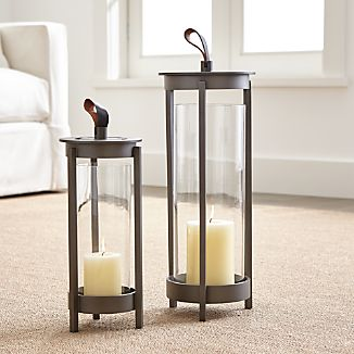 "Royce Nelson-designed metal lanterns make a spectacular show of flicker candlelight. Footed base gives candles a lift, rising in an open cylinder pewter-toned aluminum. Leather tab mixes media as a casual, practical handle.Designed by Royce NelsonAluminum with pewter finishRemovable glass insertLeather strapAccommodates up to 3""-dia. pillar candle, sold separatelyFor indoor or outdoor useMade in India"