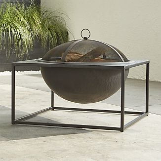 Architectural firepit adds a modern edge to the traditional iron firepit, suspending a round bowl from an open, square frame, all with a smart black, heat-resistant finish. Mesh lid keeps sparks contained, and bowl's interior is hammered to minimize the look of log dents over time. Removable grate and stand make for easy cleaning.