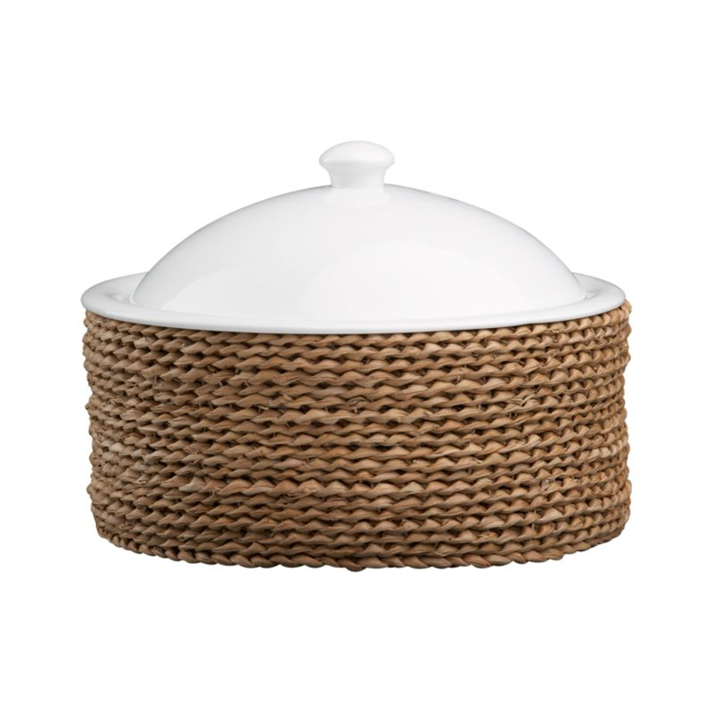 A beautiful serving solution nests an oven-to-table white porcelain lidded casserole in a rustic handwoven fiber basket. Decorative and functional, the basket serves as a trivet to protect tables and countertops, or can be used separately for breads and rolls. Perfect for passing hot dishes at the table.<br /><br /><NEWTAG/><ul><li>High fired porcelain casserole</li><li>All natural bankuang fiber basket</li><li>Basket is food safe</li><li>Dishwasher-, freezer-, microwave- and oven-safe</li><li>Clean basket with a dry cloth only</li></ul>