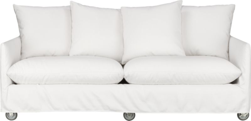"This sleek white slipcovered sofa looks like it could be right at home in a modern urban loft. But don't bother to come inside—our eco-friendly Catalina collection is designed to live carefree outdoors under blue skies. Under that UV-, fade- and moisture-resistant Sunbrella® sailcloth slipcover (yes, it's even machine-washable), you'll find a thoughtfully crafted sofa made in the USA at the same furniture workshop as many of our living room upholstered collections. A 15-ply outdoor-grade sustainable birch plywood frame subtly slopes the seat deck front to back to drain water properly from an open bottom slot. Plush cushions are a reticulated open-cell foam that allows water to drain. Comfortable back cushions and pillows are protected by waterproof ticking. Upholstered in Sunbrella base cloth sand, an open-weave fabric that accelerates drainage and allows cushions and pillows to breathe, with a bottom zipper to drain water and release moisture.<br />Six rust-resistant galvanized steel casters (two lock) allow for effortless seating rearrangements or for moving indoors out of season.<br /><br />After you place your order, we will send a fabric swatch via next day air for your final approval. We will contact you to verify both your receipt and approval of the fabric swatch before finalizing your order.<br /><br /><NEWTAG/><ul><li>Eco-friendly construction</li><li>Outdoor-grade sustainable birch plywood frame</li><li>Seat cushions are mildew-resistant, reticulated open-cell foam</li><li>Back cushions and pillows are filled with outdoor recycled fiber in a waterproof ticking</li><li>Slipcovered in 100% Sunbrella solution-dyed acrylic</li><li>Machine wash the removable slipcovers; line dry</li><li>Includes four 23"" throw pillows</li><li>See additional frame options below</li></ul>"