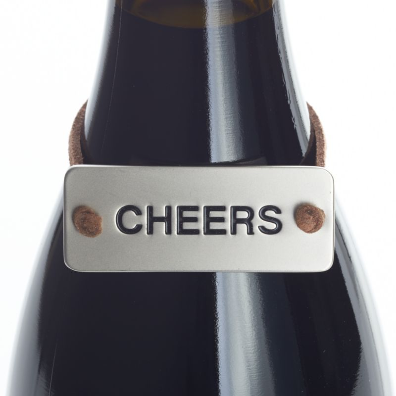 "Neat metal tag on a faux leather cord slips neatly over a gift bottle of wine, embossed to say a simple ""cheers.""<br /><br /><NEWTAG/><ul><li>Zinc with matte nickel plating</li><li>Faux leather cord</li><li>Clean with damp cloth</li><li>Made in China</li></ul>"