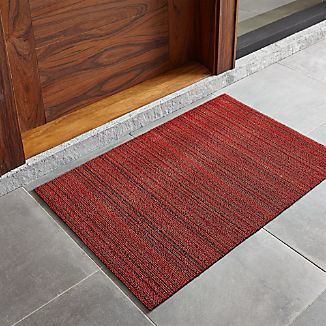 Durable, all-weather PVC and polyester are textured and looped in tonal bands of reds and neutrals. Equally at home indoors and out, this standard sized doormat is finished with vinyl backing.View all Chilewich products