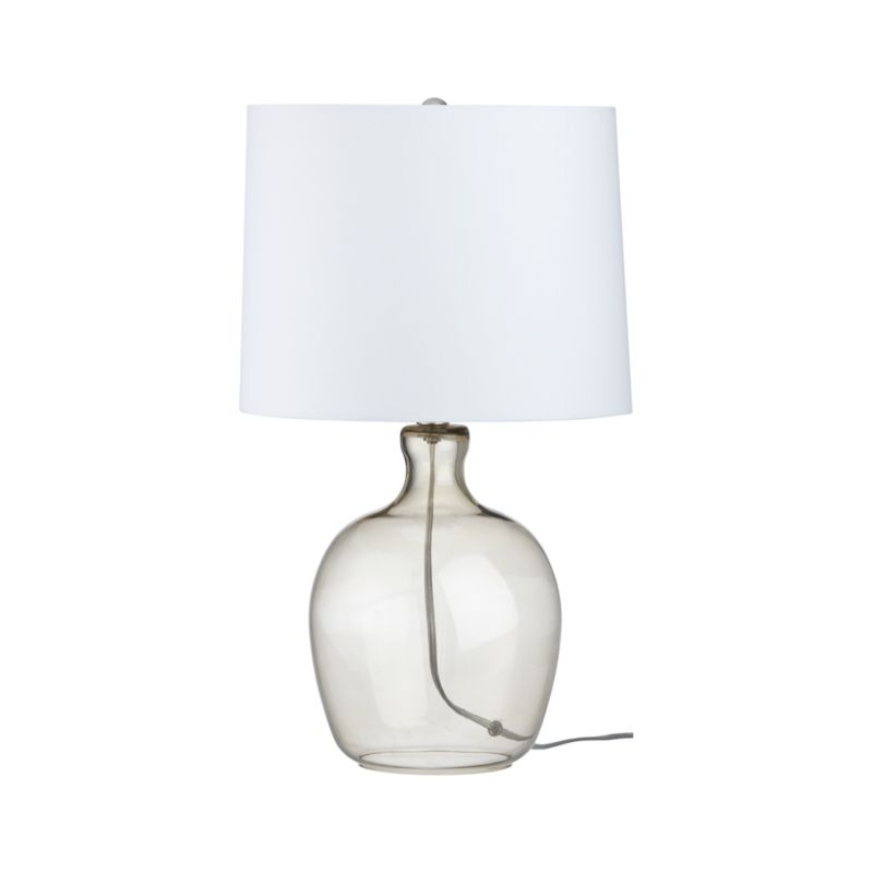 "A classic, contoured jug shape crafted in clear smoke-colored glass pairs with a cream drum shade for clean sophisticated lighting.<br /><br /><NEWTAG/><ul><li>Glass base</li><li>Clear finish</li><li>Cream poly-cotton blend shade</li><li>Brushed satin ball finial</li><li>CFL included (requires up to 23W CFL or 100W incandescent bulb)</li><li>On/off switch</li><li>60"" clear cord</li><li>Made in China</li></ul><br /><em>Note: This item is UL-Listed and manufactured in compliance with U.S. standards. If you are purchasing this item for use outside of the U.S. or Canada, use only with the appropriate outlet adaptor and voltage converter for your country. Do not plug into an electrical outlet higher than 110-120V as this could result in fire and/or injury.</em>"