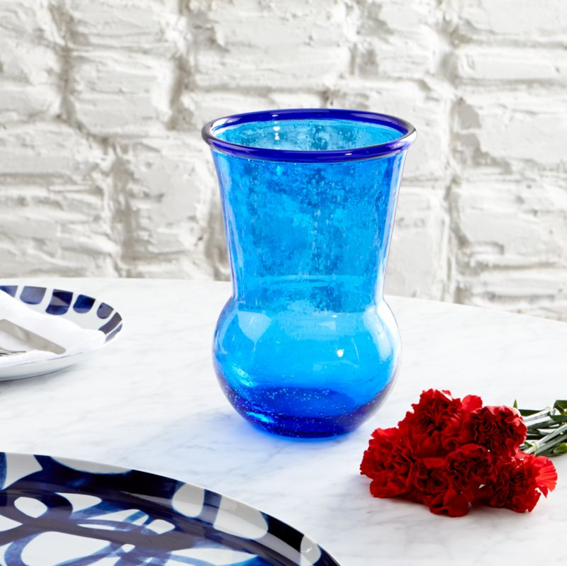 Paola Navone's palette of blues is inspired by her world experiences and life by the sea. From the deep blues found in Moroccan tiles and the Turkish eye to the aquamarine seas of the Greek Isles, a range of blues infuses the Como collection with coastal color and flair. Tulip-shaped vase bubbles like the tide, handcrafted of thick blue glass and rimmed with a ring of cobalt.<br /><br /><NEWTAG/><ul><li>Designed by Paola Navone exclusively for Crate and Barrel</li><li>Handcrafted</li><li>Glass</li><li>Hand wash</li><li>Made in Thailand</li></ul>