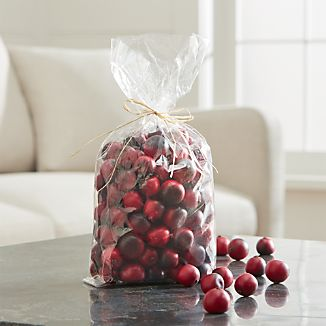 Bright red faux cranberries add a pop of seasonal color to centerpiece bowls and hurricanes, year after year.