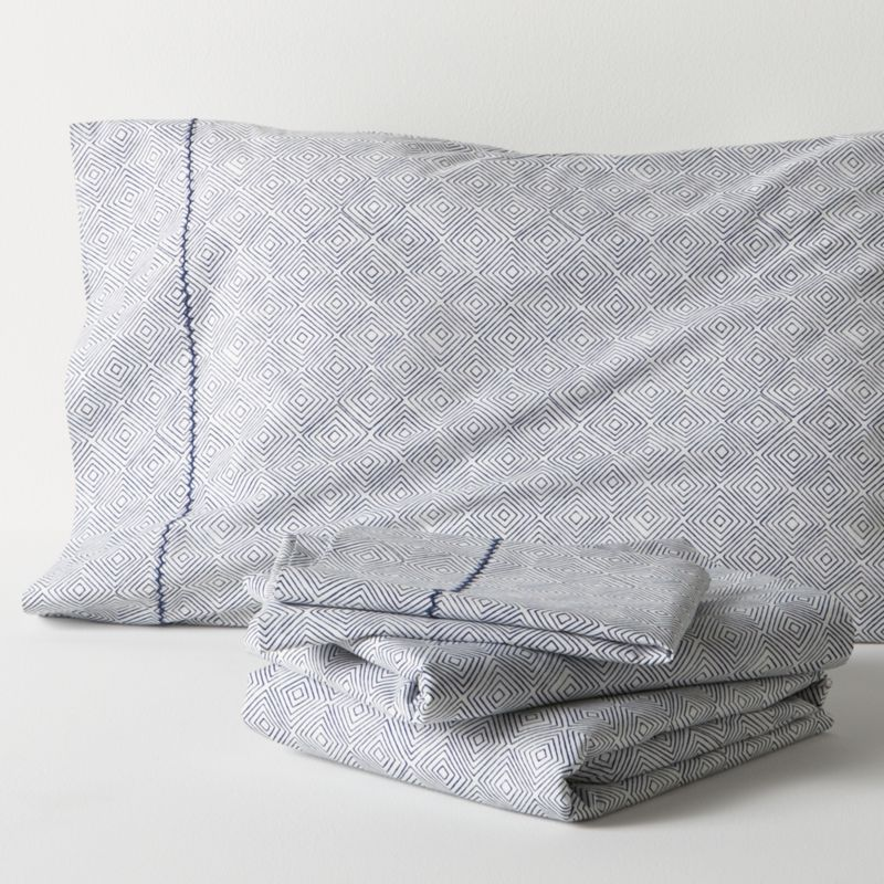 A subtle optic of concentric diamonds is screen-printed navy on neutral to layer with patterned or solid bedding. Soft cotton percale sheets are joined by matching cases, embellished with a single row of hand-embroidered chain stitching. Sheet set includes one flat sheet, one fitted sheet and two standard pillowcases. Bed pillows also available.<br /><br /><NEWTAG/><ul><li>100% cotton percale</li><li>200-thread-count</li><li>Machine wash, tumble dry low, warm iron as needed</li></ul>