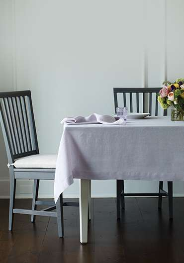Dining table with lavendar table linens and a floral centerpiece
