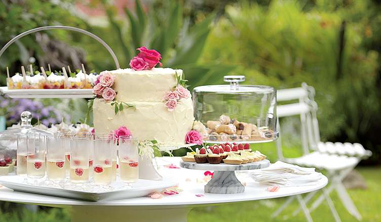 White table set outside with small desserts, cocktails and a white floral cake. Shop engagement gifts.