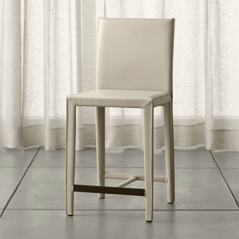In a reinvention of classic Italian design with a focus on comfort and value, our Folio counter stool gets wrapped in warm, oyster white, bonded leather. Attention-getting details make the Folio seating collection a customer favorite, including trim mitered corners, flange seaming and stitching accentuating each piece's good looks. <NEWTAG/><ul><li>Welded steel frame</li><li>Polyfoam seat cushion with fiber wrap</li><li>Mitered cut and stitched leather</li><li>Flange seaming</li><li>Grooved footrest</li><li>Made in China</li></ul>