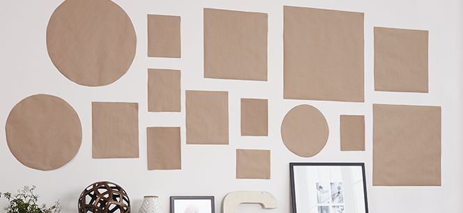 Kraft paper cutouts in the shape of frames and artwork mapped out on wall