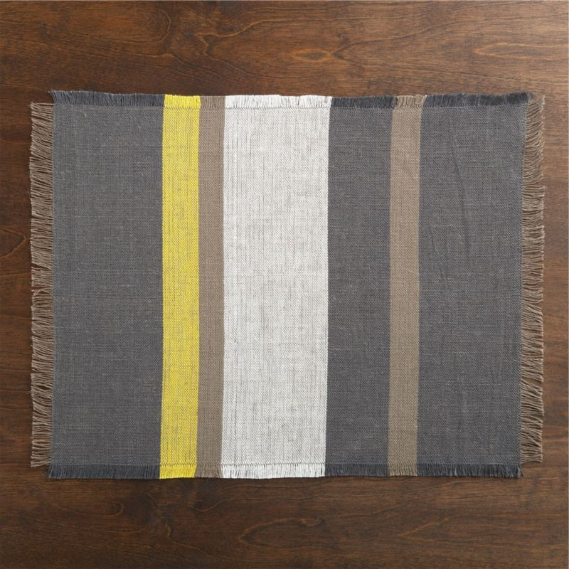 Statement-making stripes line up in grey, taupe and white, with a pop of sunny yellow. Fringe on all four sides adds a casual note to this graphic modern placemat woven of 100% linen.<br /><br /><NEWTAG/><ul><li>100% linen</li><li>Machine wash cold, line dry; warm iron as needed</li><li>Oversized to allow for shrinkage</li><li>Made in India</li></ul>