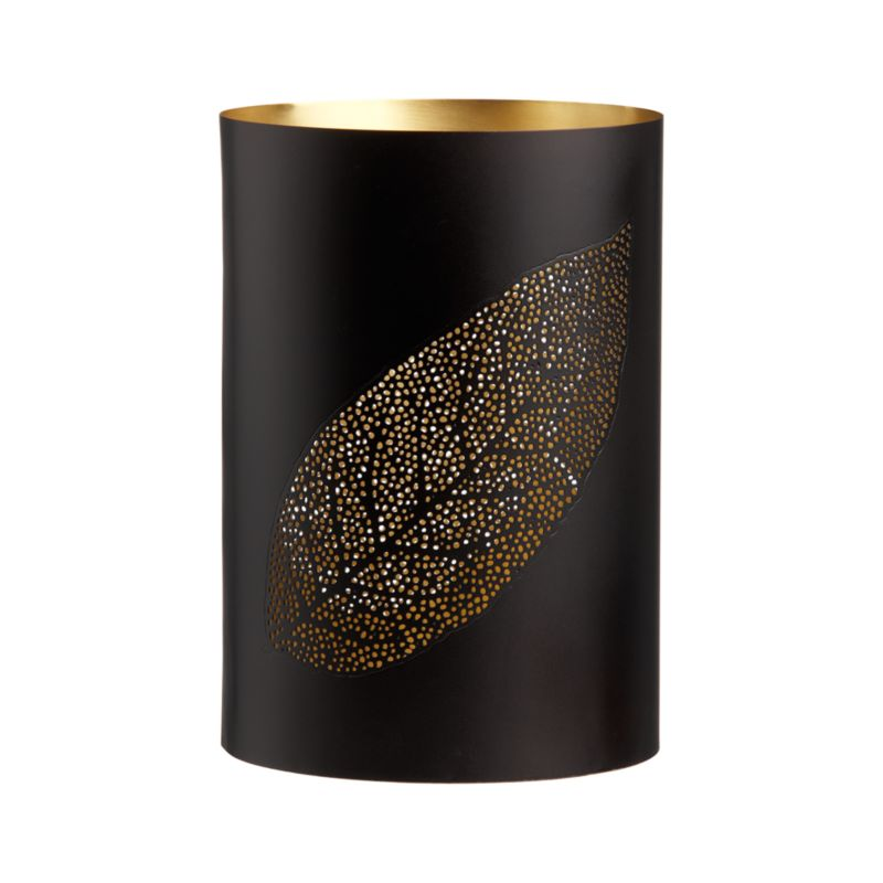 A gold-plated interior peaks through two organic leaf-shape designs created by hundreds of tiny pinholes in a matte black iron exterior. Insert candle and the drama increases. Light shines through a broad leaf pattern on one side, the thinner mango leaf shape on the other.<br /><br /><NEWTAG/><ul><li>Iron</li><li>Gold plate</li><li>Candleholder accommodates a standard votive or tealight candle, sold separately</li><li>Made in India</li></ul><br />