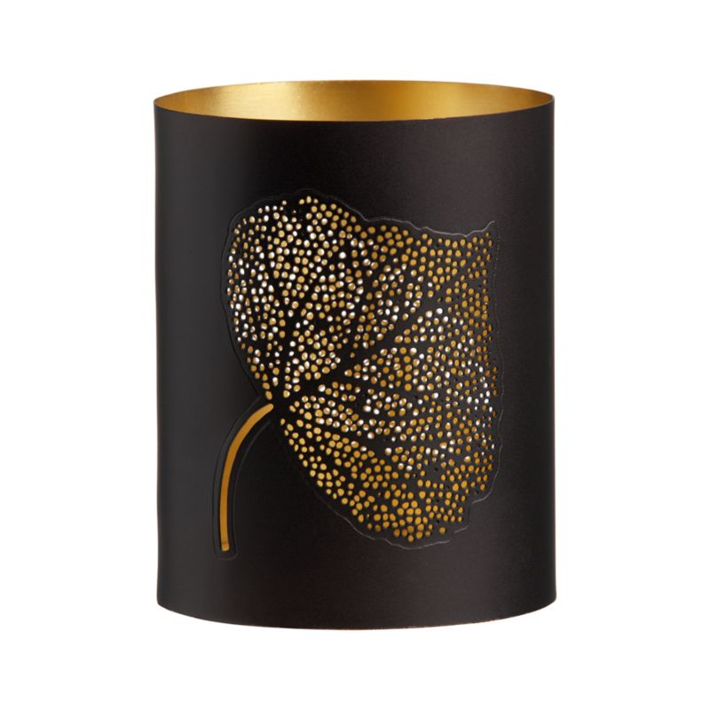 "A gold-plated interior peaks through two organic leaf-shape designs created by hundreds of tiny pinholes in a matte black iron exterior. Insert candle and the drama increases. Light shines through a broad leaf pattern on one side, the thinner mango leaf shape on the other.<br /><br /><NEWTAG/><ul><li>Iron</li><li>Gold plate</li><li>Hurricane accommodates up to a 3"" pillar candle, sold separately</li><li>Made in India</li></ul><br />"