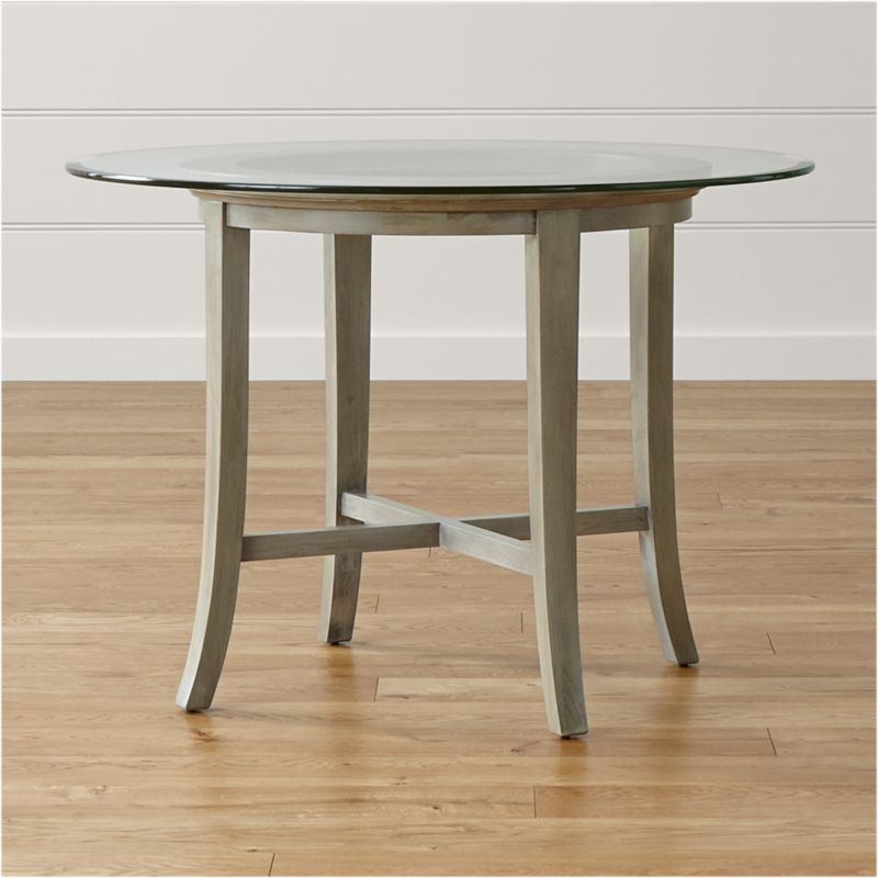 "With its distinctive ""halo"" effect, this striking table features a flat glass top with a deep, light-refracting reverse bevel that's echoed in the open ring of the solid chestnut wood base. Featuring a cross brace and slightly flared legs, the table is constructed using traditional wood-on-wood joinery without the use of screws or nails.  <NEWTAG/><ul><li>Solid chestnut base with grey-washed lacquer finish</li><li>Clear ½""-thick glass top with reverse bevel and polished edge</li><li>BreathingJoinery ™</li><li>Plastic glides</li><li>Seats four</li><li>Made in China</li></ul>"
