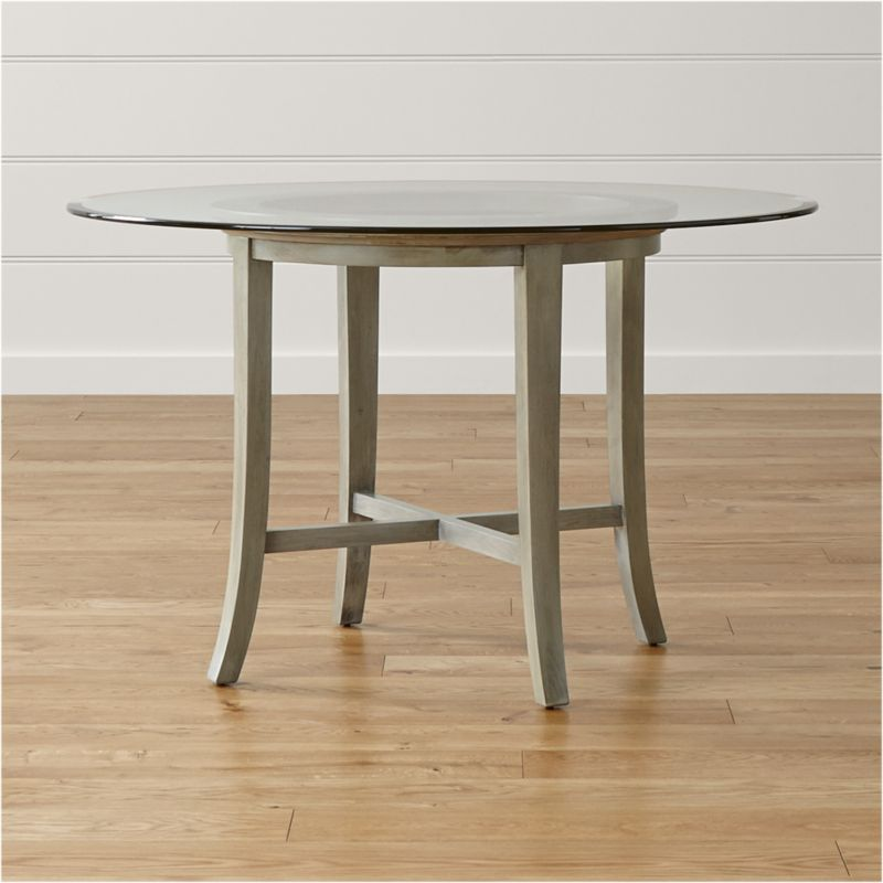 "With its distinctive ""halo"" effect, this striking table features a flat glass top with a deep, light-refracting reverse bevel that's echoed in the open ring of the solid chestnut wood base. Featuring a cross brace and slightly flared legs, the table is constructed using traditional wood-on-wood joinery without the use of screws or nails. <NEWTAG/><ul><li>Solid chestnut base with grey-washed lacquer finish</li><li>Clear ½""-thick glass top with reverse bevel and polished edge</li><li>BreathingJoinery ™</li><li>Plastic glides</li><li>Seats 4</li><li>Made in China</li></ul>"