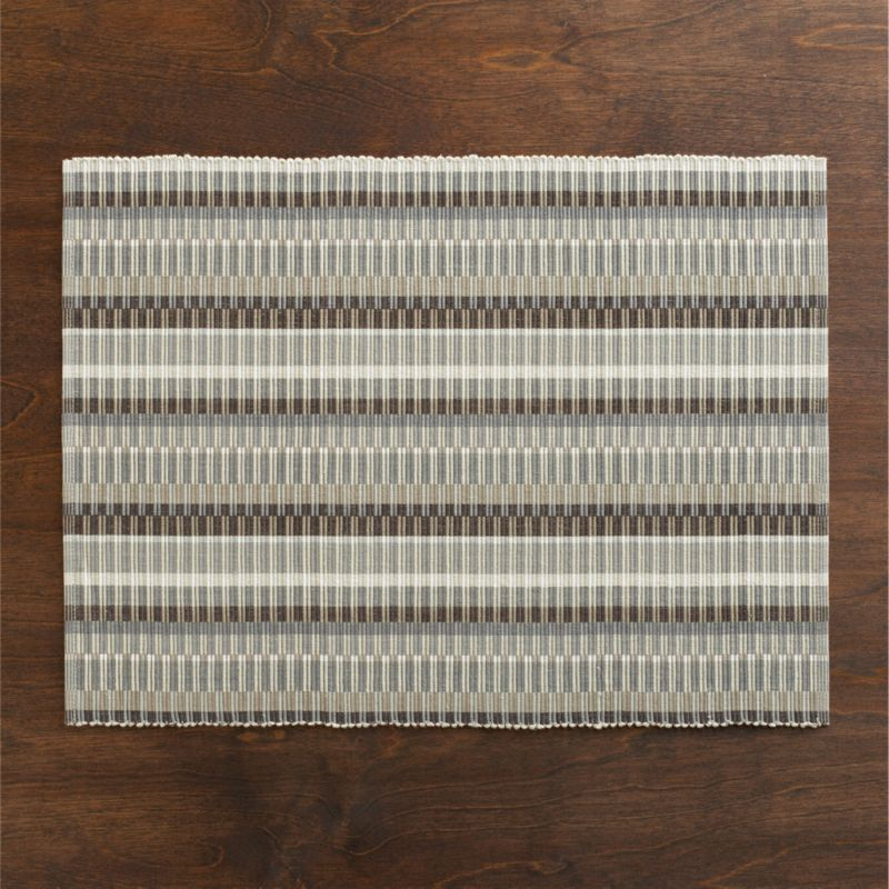 Staggered rows of neutral stripes make minimalist play of traditional African coiled basket design, channeling repeats into a mesmerizing ribbed pattern hand-woven of hand-dyed cotton. Placemat is oversized to allow for shrinkage.<br /><br /><NEWTAG/><ul><li>Handcrafted</li><li>100 % cotton</li><li>Machine wash, reshape and dry flat; warm iron as needed</li><li>Made in India</li></ul>