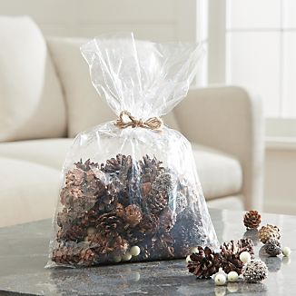 Pinecones, pods, white berries and bits, both real and faux, fill vases with organic sparkle or spill down a runner for an intriguing, seasonal tablescape.
