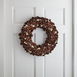 Pinecones take on just the right amount of sparkle to make this nature-derived wreath extra festive. Pods and faux white berries add a bit of color and textural interest in this large pinecone wreath.
