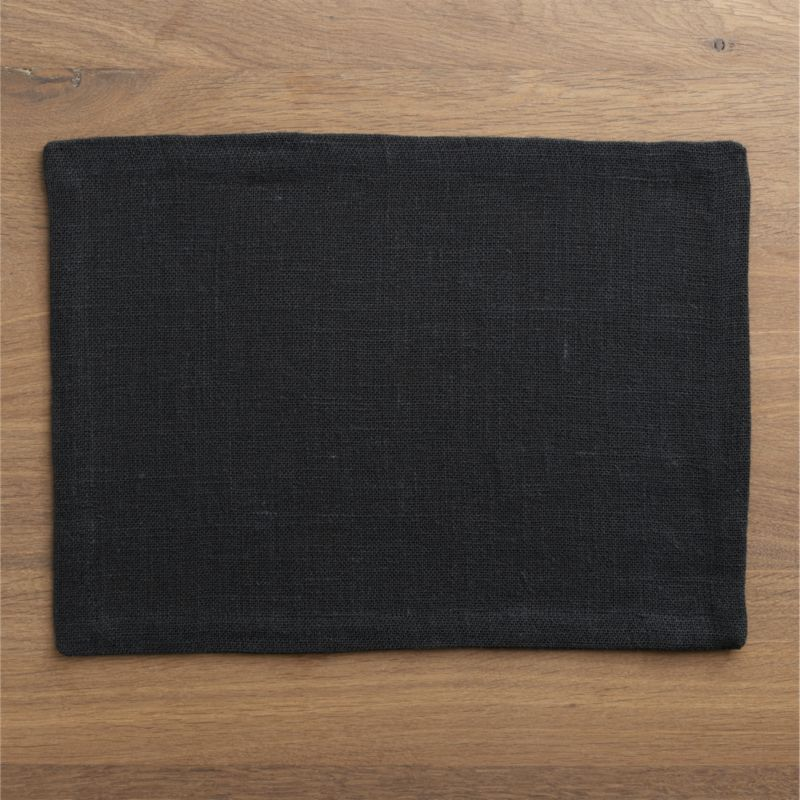 Casual jute attires in an open weave of soft black with the relaxed style of unpressed linen. Placemat is tailored with a generous hem and mitered corners. Fiber will soften with each wash.<br /><br /><NEWTAG/><ul><li>Jute</li><li>Machine wash, reshape and dry flat; warm iron as needed</li><li>Made in India</li></ul>