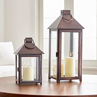 "The traditional lantern scales up and streamlines with a warm bronze finish that looks great in the home or outside on the patio. Clean and classic styling includes glass panels, a hinged door, and hanging handle. Pair the coordinating lanterns together for a multi-level approach to candlelight.Iron with bronze finishGlass panelsFor indoor or outdoor useAccommodate up to a 3""-diameter pillar candle, sold separatelyMade in India"