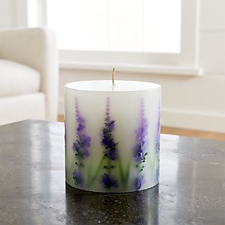 Realistic lavender blossoms embedded in a white pillar candle create a nature-inspired look.  Scented with lavender, the candle makes a lovely hostess or Mother's Day gift.