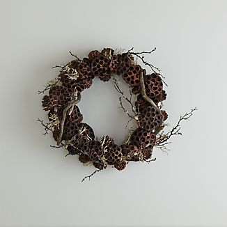 Our striking twig wreath combines traditional pinecones with unexpected lotus to showcase fall's enchanting forms. Hang on the wall or in a sheltered outdoor space for a unique botanical accent.