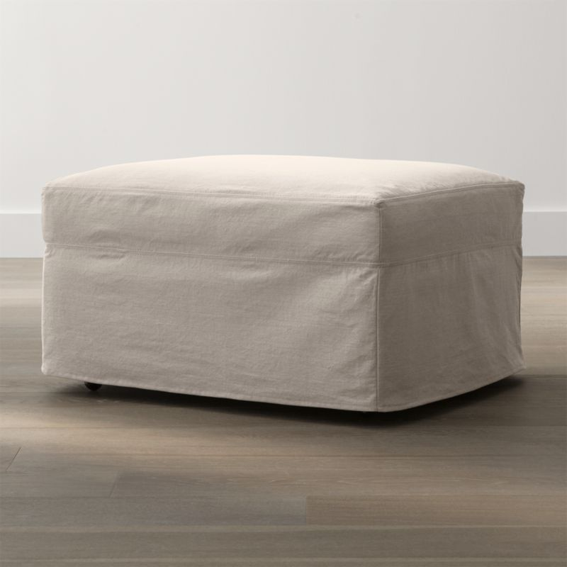 """Tailored to fit our Lounge Slipcovered Ottoman, smart denim slipcover is tailored with a kickpleat skirt and jumbo double topstitch outlining.<br /><br />Additional <a href=""""http://crateandbarrel.custhelp.com/cgi-bin/crateandbarrel.cfg/php/enduser/crate_answer.php?popup=-1&p_faqid=125&p_sid=DMUxFvPi"""">slipcovers</a> available below and through stores featuring our Furniture Collection.<br /><br />After you place your order, we will send a fabric swatch via next day air for your final approval. We will contact you to verify both your receipt and approval of the fabric swatch before finalizing your order.<br /><br /><NEWTAG/><ul><li>100% cotton</li><li>Machine washable</li><li>Jumbo contrast saddle stitch detail</li><li>Made in North Carolina, USA of domestic and imported materials</li></ul><br /><br />"""