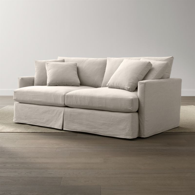 """Tailored to fit our Lounge 83"""" Sofa, smart denim slipcover is tailored with a kickpleat skirt and jumbo double topstitch outlining its high slim arm and plump, deep cushions.<br /><br />Additional <a href=""""http://crateandbarrel.custhelp.com/cgi-bin/crateandbarrel.cfg/php/enduser/crate_answer.php?popup=-1&p_faqid=125&p_sid=DMUxFvPi"""">slipcovers</a> available below and through stores featuring our Furniture Collection.<br /><br />After you place your order, we will send a fabric swatch via next day air for your final approval. We will contact you to verify both your receipt and approval of the fabric swatch before finalizing your order.<br /><br /><NEWTAG/><ul><li>100% cotton</li><li>Machine washable</li><li>Jumbo contrast saddle stitch detail</li><li>Made in North Carolina, USA of domestic and imported materials</li></ul><br />"""