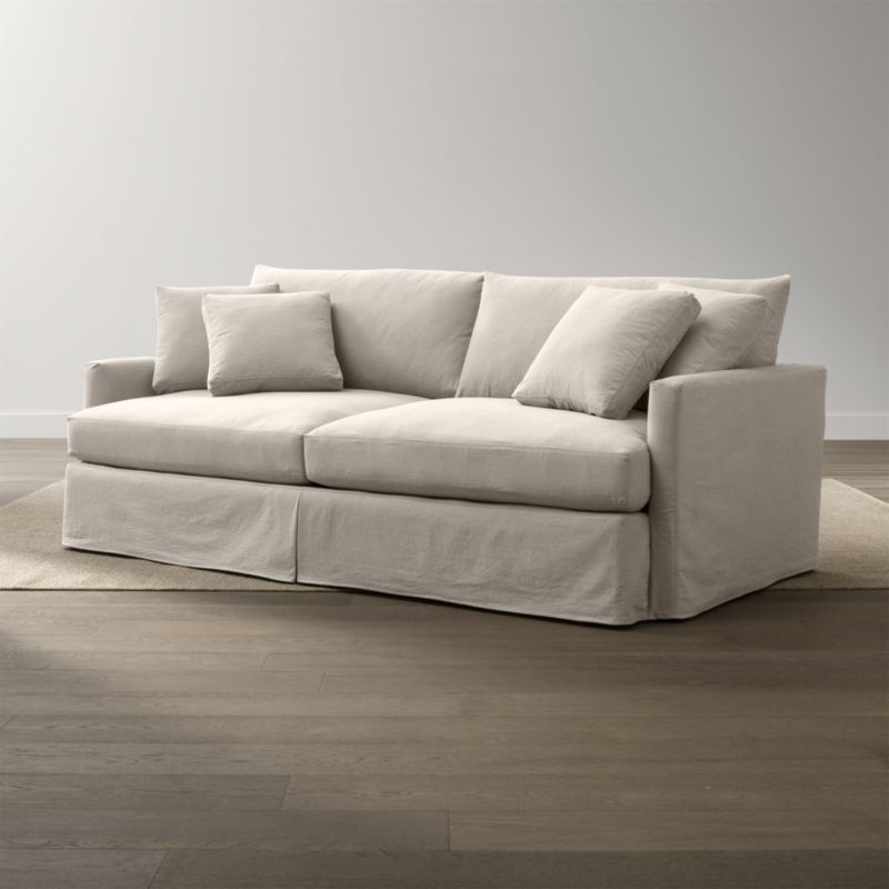 """Tailored to fit our Lounge 93"""" Sofa, smart denim slipcover is tailored with a kickpleat skirt and jumbo double topstitch outlining its high slim arm and plump, deep cushions.<br /><br />Additional <a href=""""http://crateandbarrel.custhelp.com/cgi-bin/crateandbarrel.cfg/php/enduser/crate_answer.php?popup=-1&p_faqid=125&p_sid=DMUxFvPi"""">slipcovers</a> available below and through stores featuring our Furniture Collection.<br /><br />After you place your order, we will send a fabric swatch via next day air for your final approval. We will contact you to verify both your receipt and approval of the fabric swatch before finalizing your order.<br /><br /><NEWTAG/><ul><li>100% cotton</li><li>Machine washable</li><li>Jumbo contrast saddle stitch detail</li><li>Made in North Carolina, USA of domestic and imported materials</li></ul><br />"""