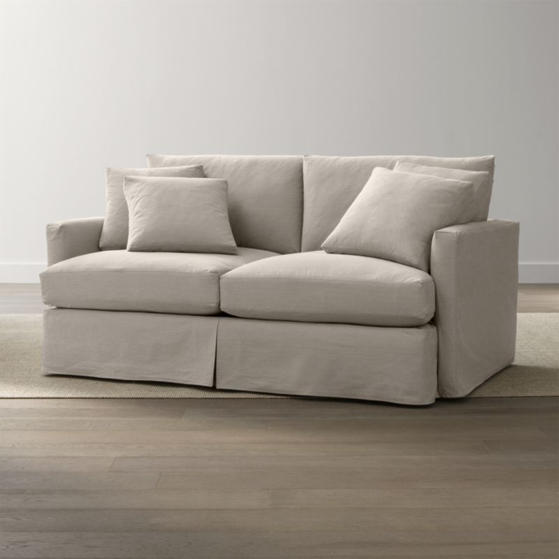 """Tailored to fit our Lounge Slipcovered Left Arm Chair, smart denim slipcover is tailored with a kickpleat skirt and jumbo double topstitch outlining its high slim arm and plump, deep cushions.<br /><br />Additional <a href=""""http://crateandbarrel.custhelp.com/cgi-bin/crateandbarrel.cfg/php/enduser/crate_answer.php?popup=-1&p_faqid=125&p_sid=DMUxFvPi"""">slipcovers</a> available below and through stores featuring our Furniture Collection.<br /><br />After you place your order, we will send a fabric swatch via next day air for your final approval. We will contact you to verify both your receipt and approval of the fabric swatch before finalizing your order.<br /><br /><NEWTAG/><ul><li>100% cotton</li><li>Machine washable</li><li>Jumbo contrast saddle stitch detail</li><li>Made in North Carolina, USA of domestic and imported materials</li></ul><br />"""